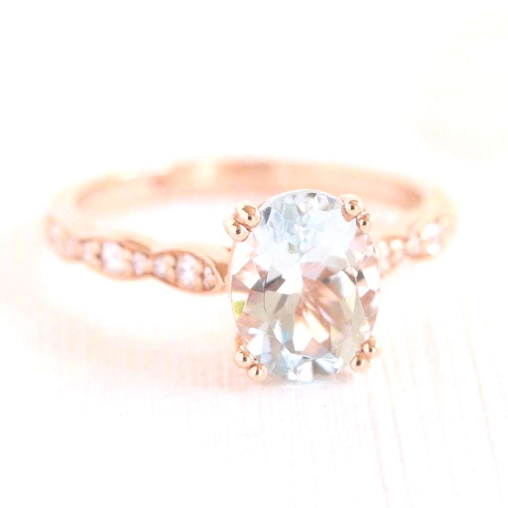Graceful solitaire engagement ring features an oval cut aquamarine set in rose gold scalloped diamo