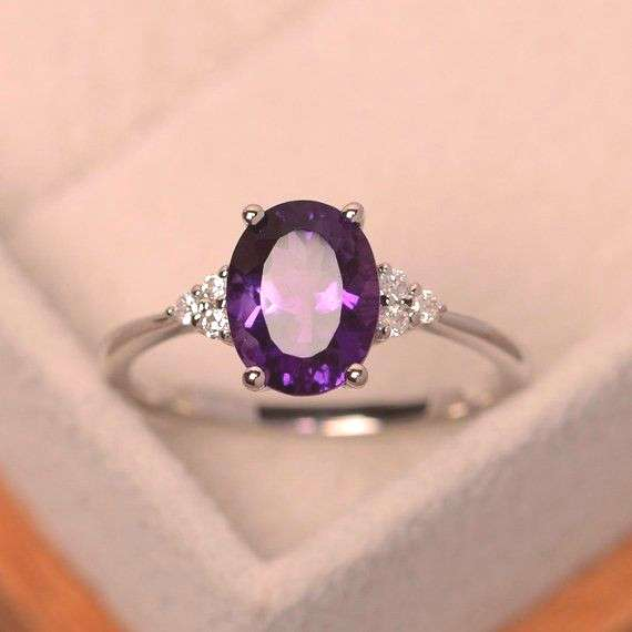 This ring features a 7mm*9mm oval cut amethyst and sterling silver finished with rhodium. Customiza